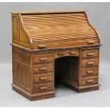 A modern hardwood roll-top desk, the tambour shutter above slides and drawers, height 125cm, width