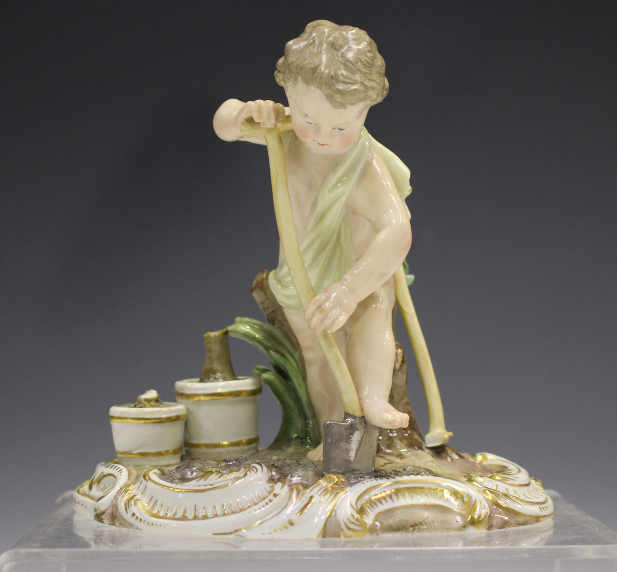 A Meissen figure of a putto gardener, late 19th century, modelled digging with a spade, a rake and