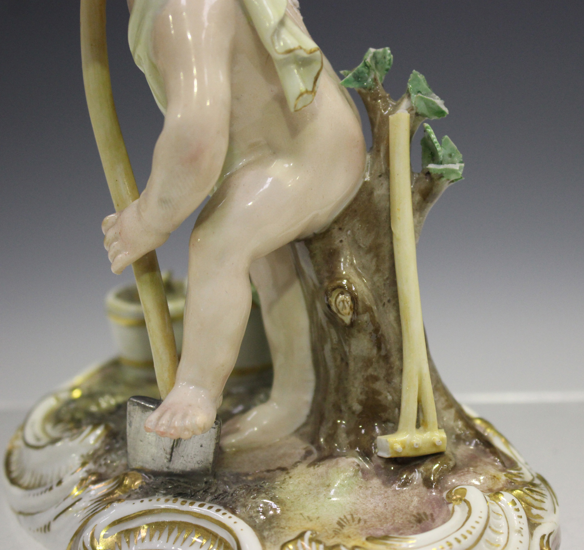 A Meissen figure of a putto gardener, late 19th century, modelled digging with a spade, a rake and - Image 3 of 7