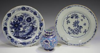 A Dutch Delft plate, 19th century, blue painted with flowers, diameter 22.5cm, together with an