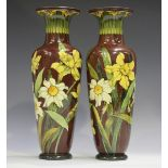 A pair of Doulton Lambeth faience pottery vases, circa 1873-1914, each slender body decorated by C.