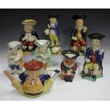 A Staffordshire Toby teapot and cover, height 18.5cm, together with seven Toby jugs, late 19th