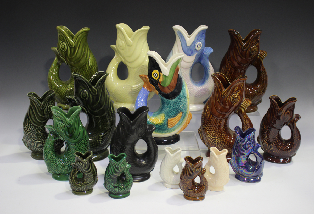A collection of gurgling fish jugs, mostly Dartmouth or Persabus potteries, various colours and