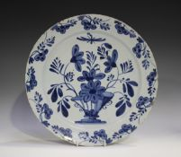 An English Delft charger, 18th century, painted in blue with a vase and flowers, the rim similarly