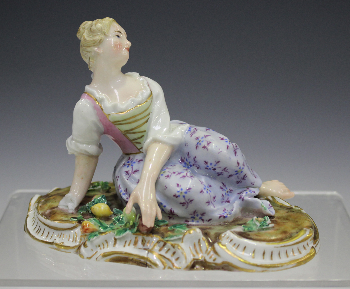 A Meissen figure of a recumbent girl, late 19th century, modelled on a naturalistic base with gilt