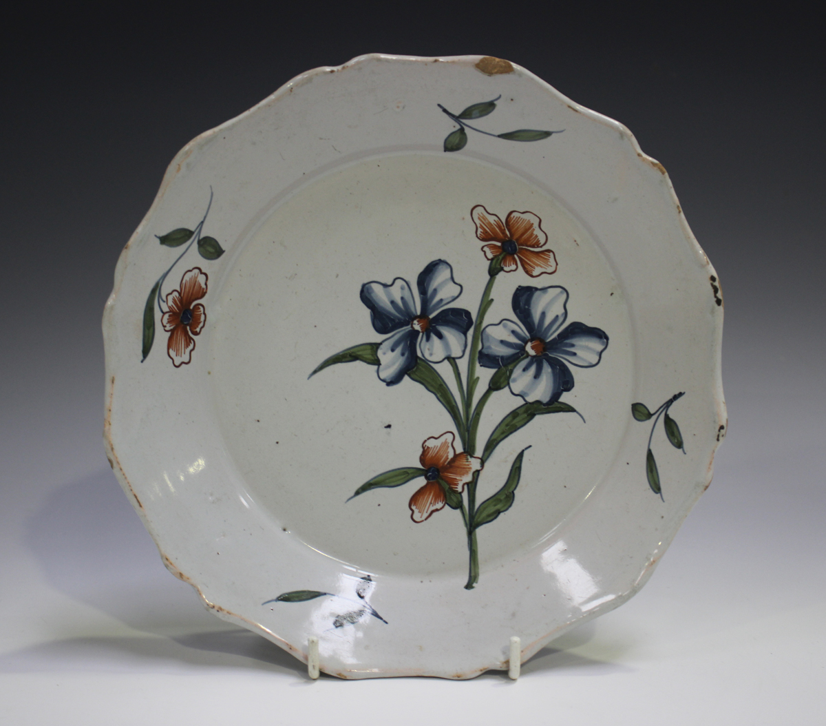 A Delft plate, 18th century, painted in blue, green and red with a floral spray, diameter 22.5cm (