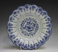 A Delft moulded dish, 18th century, painted in blue with flowers, the fluted rim with a continuous