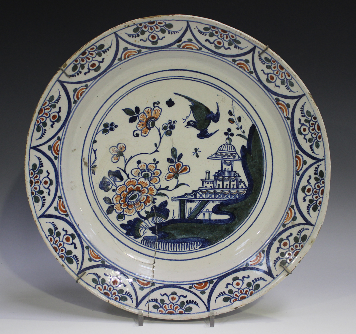 An English Delft charger, Bristol, 18th century, painted in blue, green and red with a chinoiserie