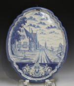 A large Dutch Delft wall plaque, late 19th/early 20th century, of shaped oval form, painted in