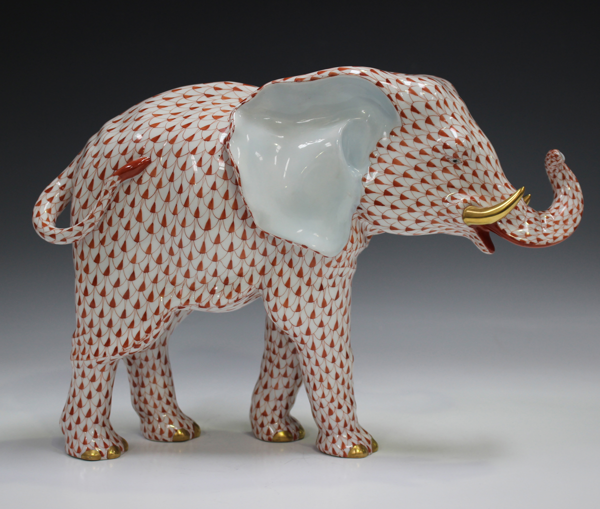 A large Herend porcelain elephant with iron red scale decoration, impressed and printed marks to