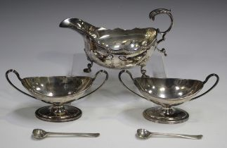 A pair of Victorian silver table salts, each of oval boat shaped form with reeded rims and loop