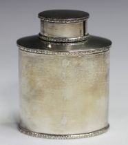 A George V silver oval tea caddy and cover, decorated in relief with foliate bands, Birmingham