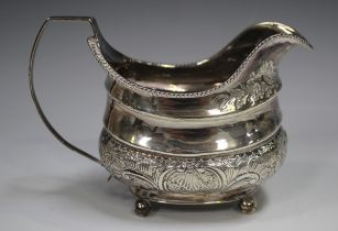 A George III silver cream jug of cushion form with gadrooned rim above a band of foliate scrolls,