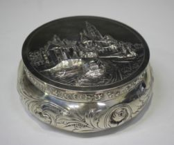 An early 20th century Dutch silver circular box with hinged lid, embossed with buildings and figures
