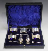 A George V silver seven-piece condiment set of oval form, comprising four salts, each raised on