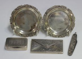 An Edwardian silver rectangular card case of envelope form, engraved with flowers and scrolls,