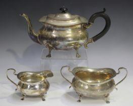 A George V silver three-piece tea set of cushion form, raised on scroll legs, comprising teapot,