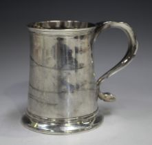A George II silver mug of tapering cylindrical form with scroll handle above a flared base,