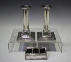 A pair of George V silver candlesticks, each cylindrical stem with anthemion decoration, on a square