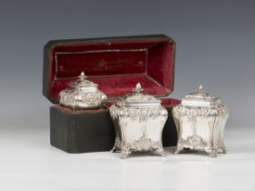 A set of three George III silver graduated tea caddies and covers with strawberry finials, each of