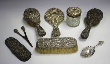 An Edwardian silver mounted six-piece dressing table set, embossed with mask and foliate scrolls,