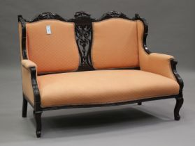A Victorian walnut showframe salon suite, carved with acanthus leaf sprays, upholstered in pink