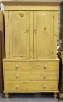 A late Victorian pine linen press, fitted with a pair of panel doors above two short and two long