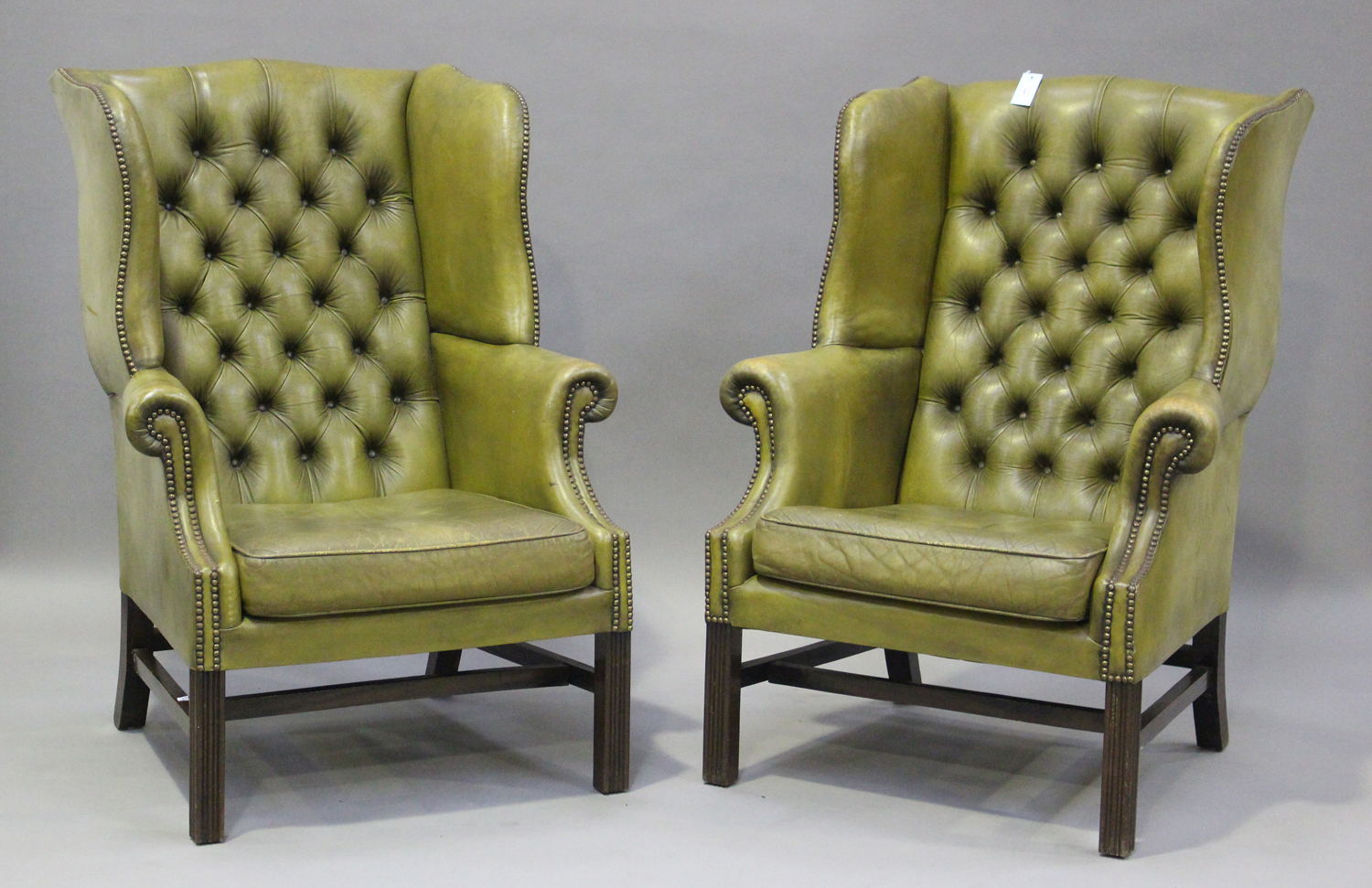 A pair of 20th century George III style wing back armchairs, upholstered in buttoned green