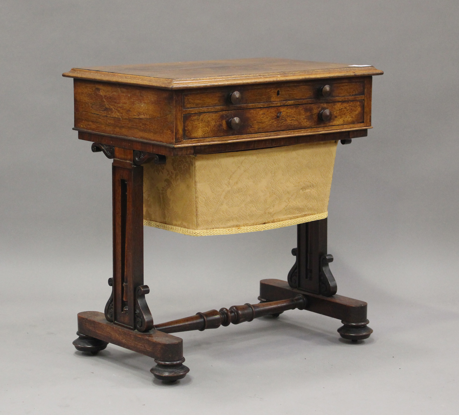 A Regency rosewood work table, the hinged lid above a drawer and basket, on scroll supports and