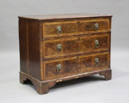 An 18th century oak and walnut chest of three drawers with crossbanded borders, on bracket feet,