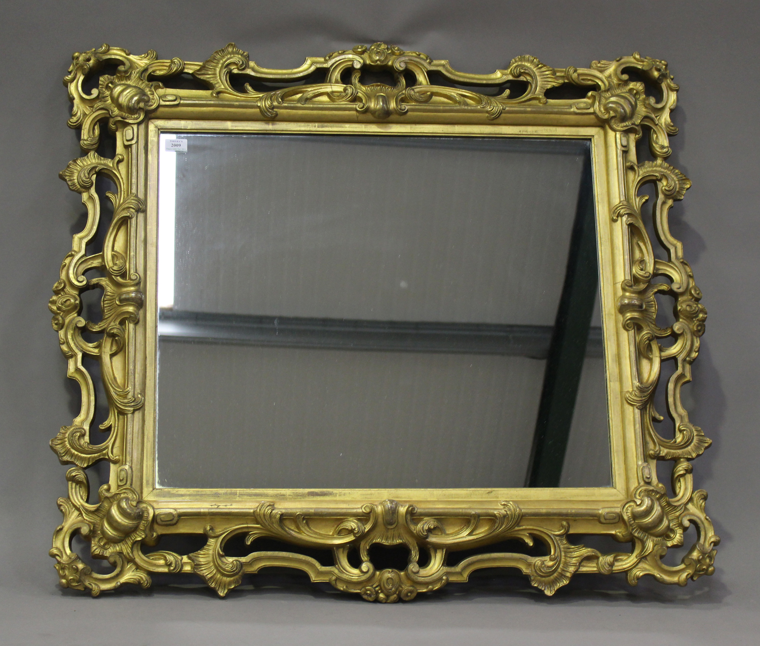 A mid/late Victorian carved gilt wood and gesso framed wall mirror, decorated with leaf and 'C'