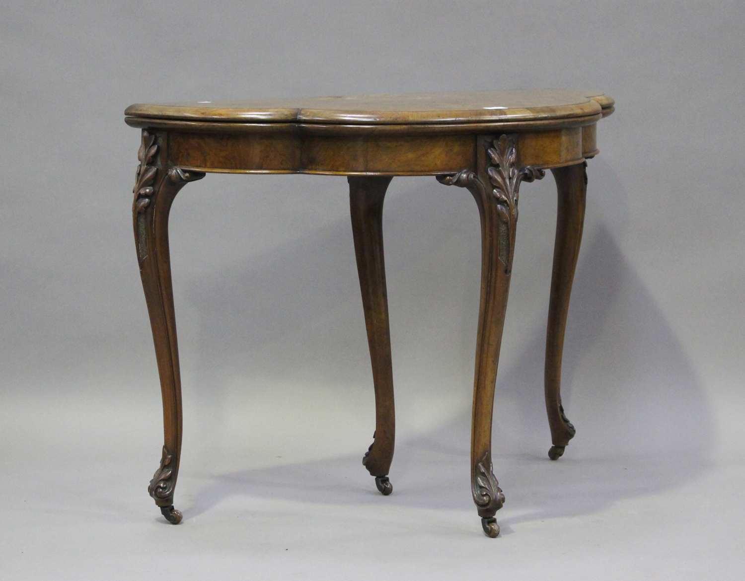 A mid-Victorian walnut fold-over card table with foliate inlaid decoration, on carved cabriole legs,