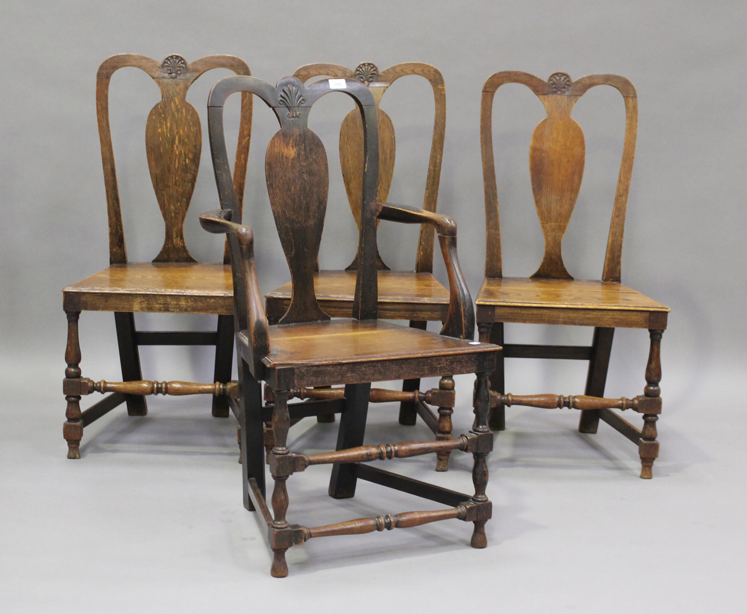 A set of four early 18th century provincial oak splat back dining chairs, the solid seats on