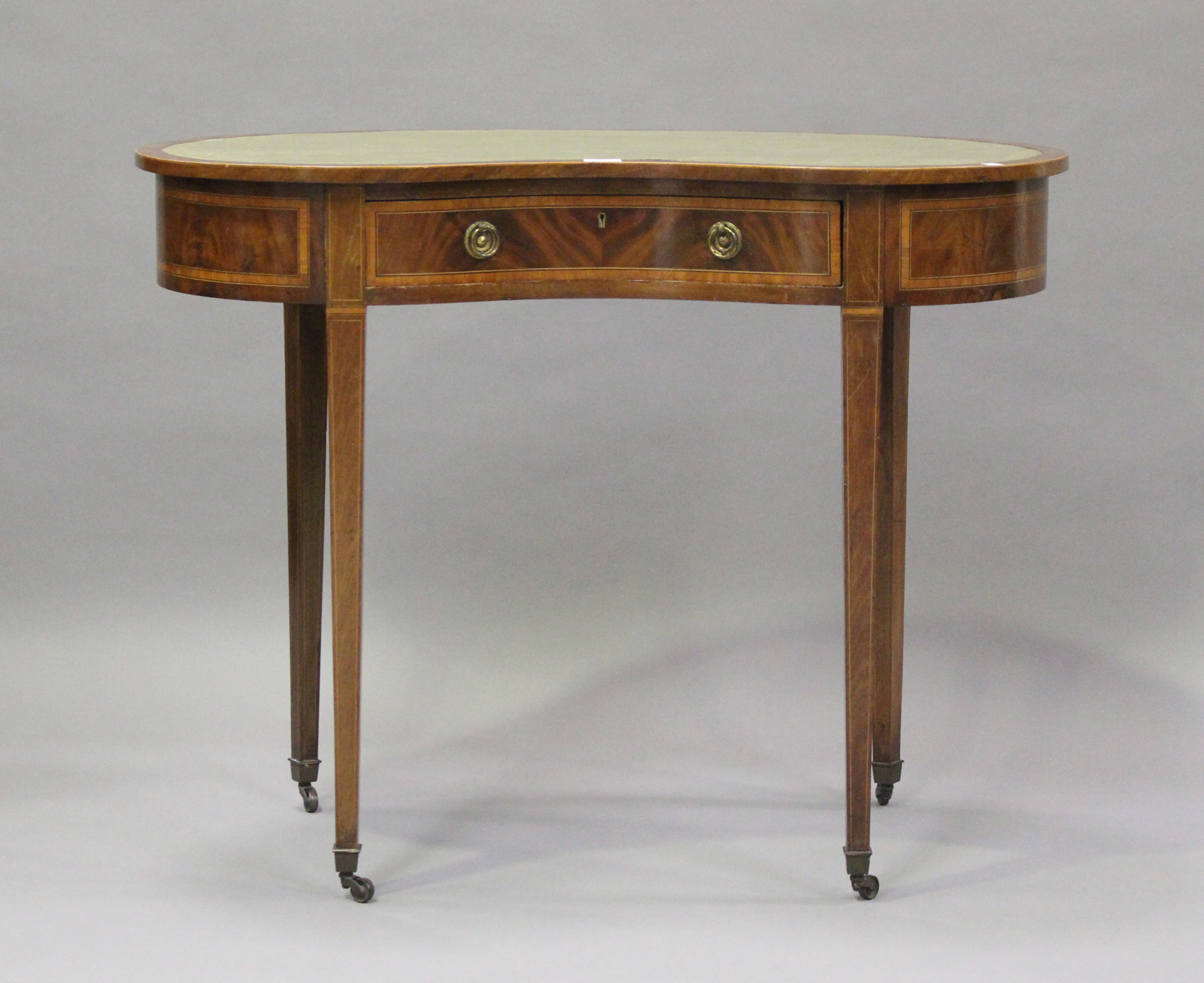 An Edwardian mahogany kidney shaped writing table, crossbanded in satinwood, fitted with a single