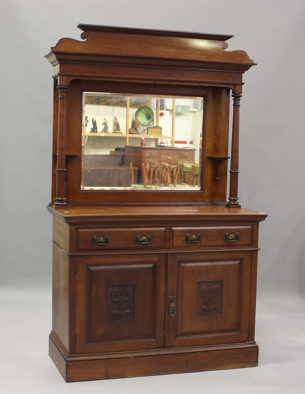 An Edwardian Arts and Crafts mahogany mirror back side cabinet, fitted with two drawers above a