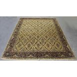 An Indian carpet, mid/late 20th century, the ivory field with an overall floral lattice, within a