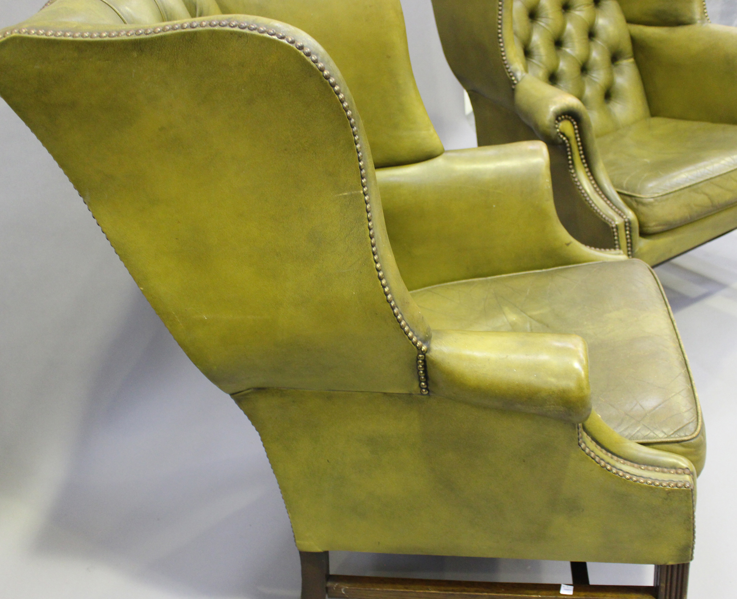 A pair of 20th century George III style wing back armchairs, upholstered in buttoned green - Image 7 of 10