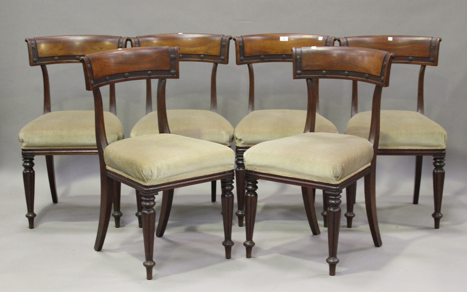 A set of six William IV mahogany bar back dining chairs with carved rosette decoration, the