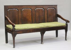 A George III oak settle with four panel back, on turned legs and pad feet, height 102cm, length