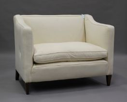 An early 20th century two-seat wing back settee, upholstered in calico, on square tapering block