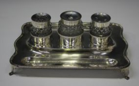 A George III silver inkstand of shaped rectangular form with gadrooned rim and two pen recesses,