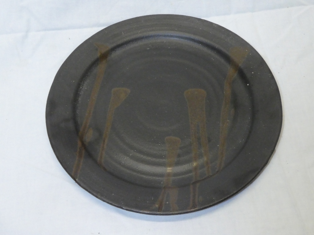 """A Studio pottery circular platter with brown glazed decoration, signed """"MW"""","""
