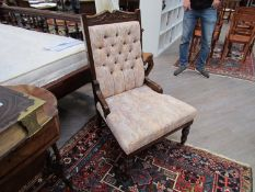 An Edwardian open armchair with button back on turned front legs to castors