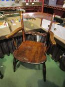 Circa 1850, a Suffolk elm knife back elbow chair with carved bar rest on ring turned legs,