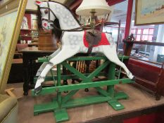A carved wooden rocking horse with dappled paintwork, on trestle rocker, 92cm wide,