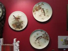 A set of three handpainted chargers decorated with birds,
