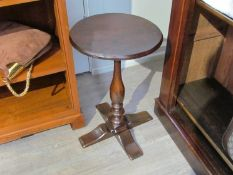 An 18th Century oak wine table the chamfered edge circular top on a turned baluster column and