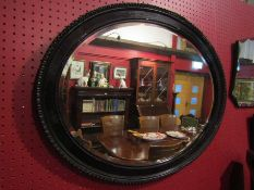 A Victorian ebonised oval mirror,
