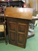 An early 20th Century oak cabinet, lift up and drop down top over cupboard base,