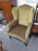 A George IV wingback armchair with ball and claw feet on castors,